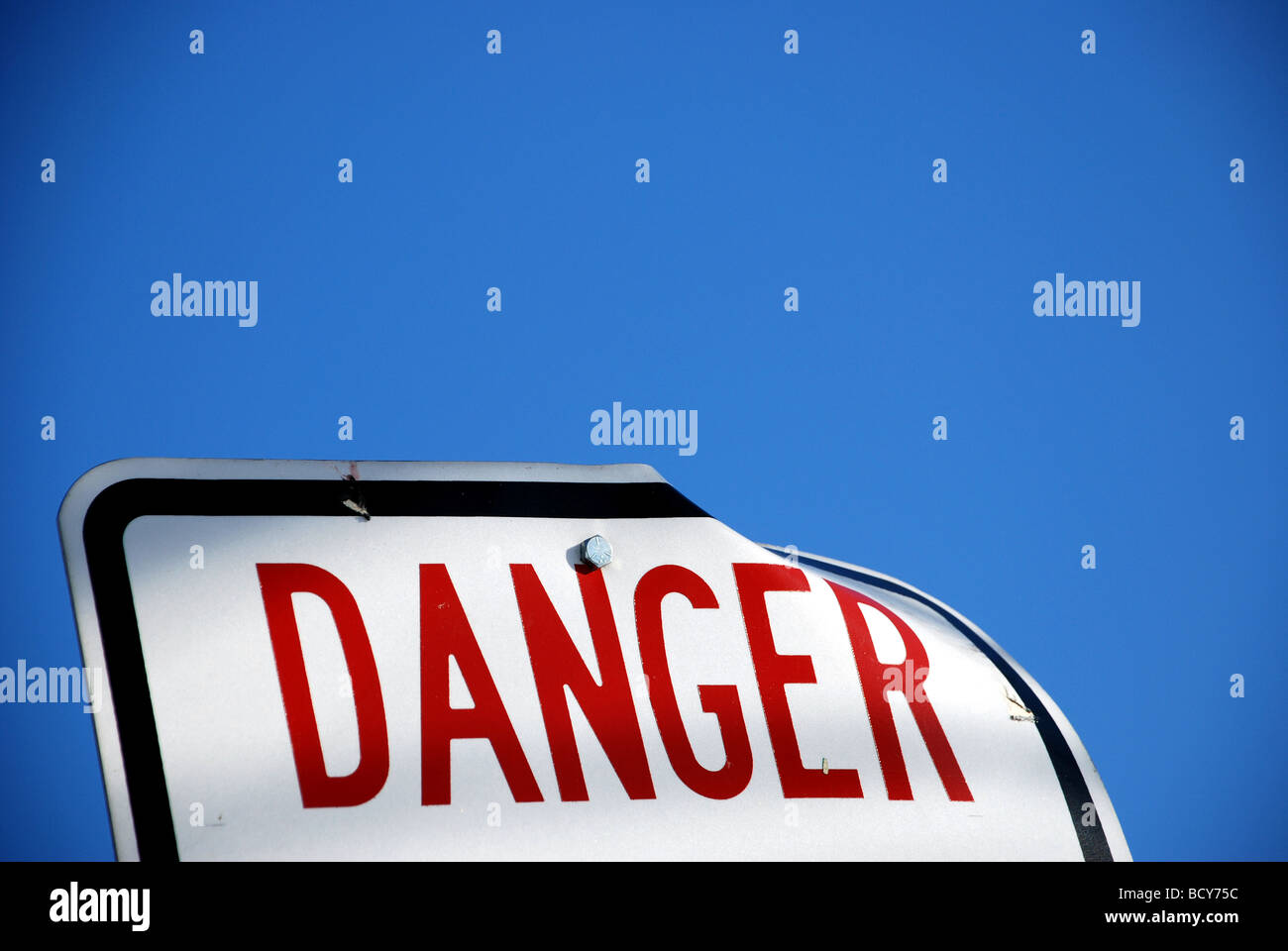 White sign with red type saying DANGER with blue sky in background - Stock Image