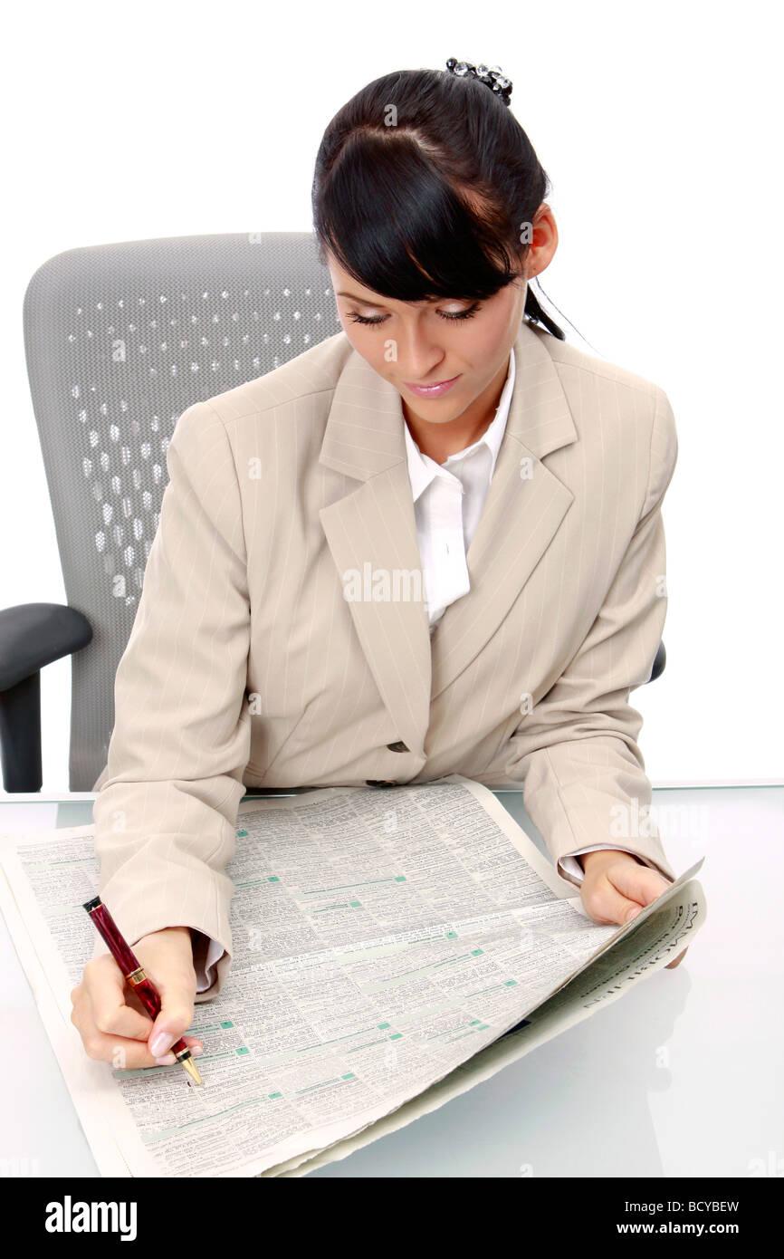 Junge Frau liest Anzeigen in der Zeitung Businesswoman reading newspaper - Stock Image