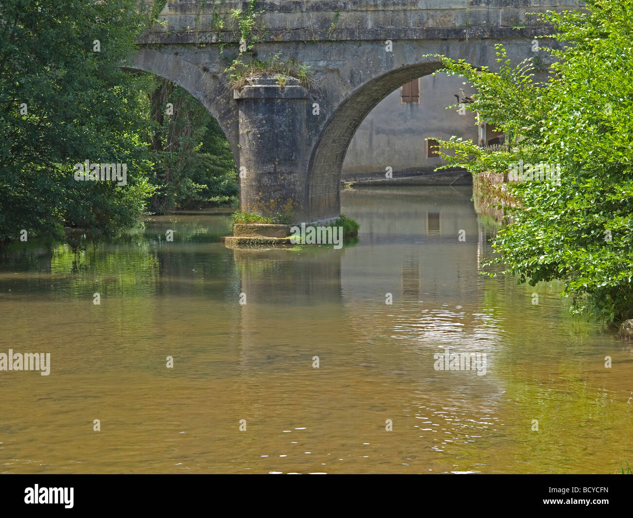 river Lot under the old stony bridge with trees by Castelfranc in France Stock Photo