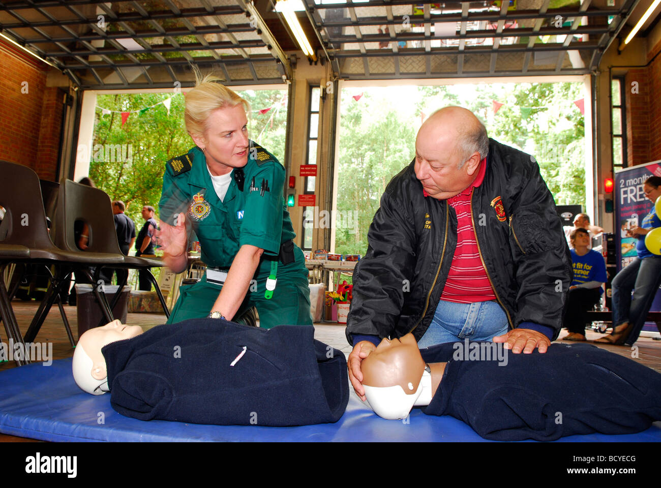 Female paramedic demonstrating CPR (Cardio Pulminary Resuscitation) to visitors at a fire station open day, Bordon, - Stock Image