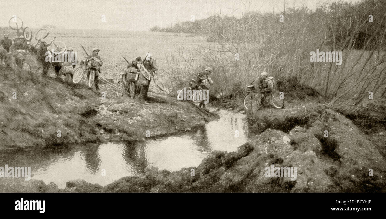 Cyclists from a French cavalry unit cross a stream with full kit. - Stock Image