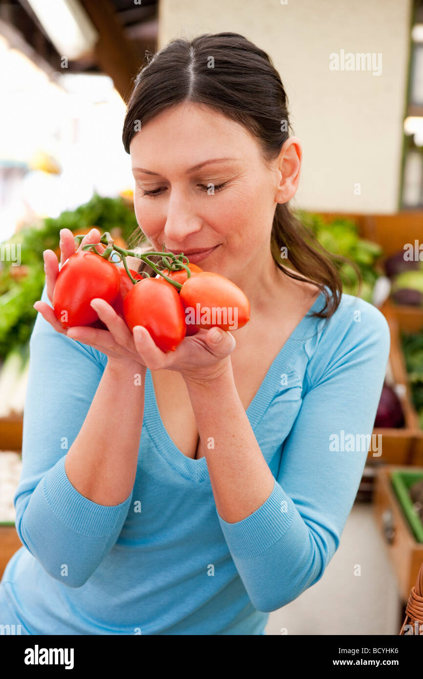 Woman taking smell at fresh tomatoes - Stock Image
