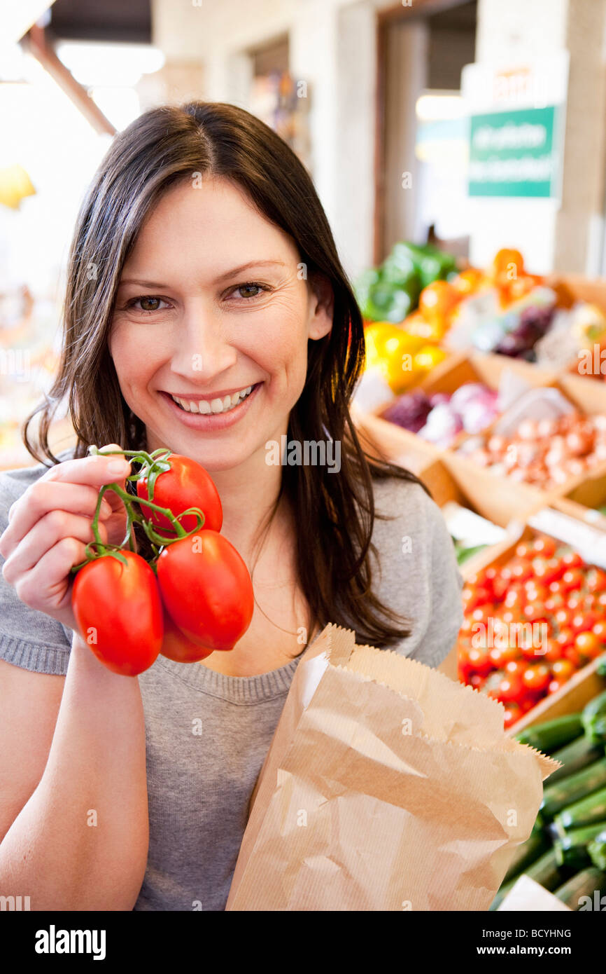 Woman showing fresh tomatoes - Stock Image
