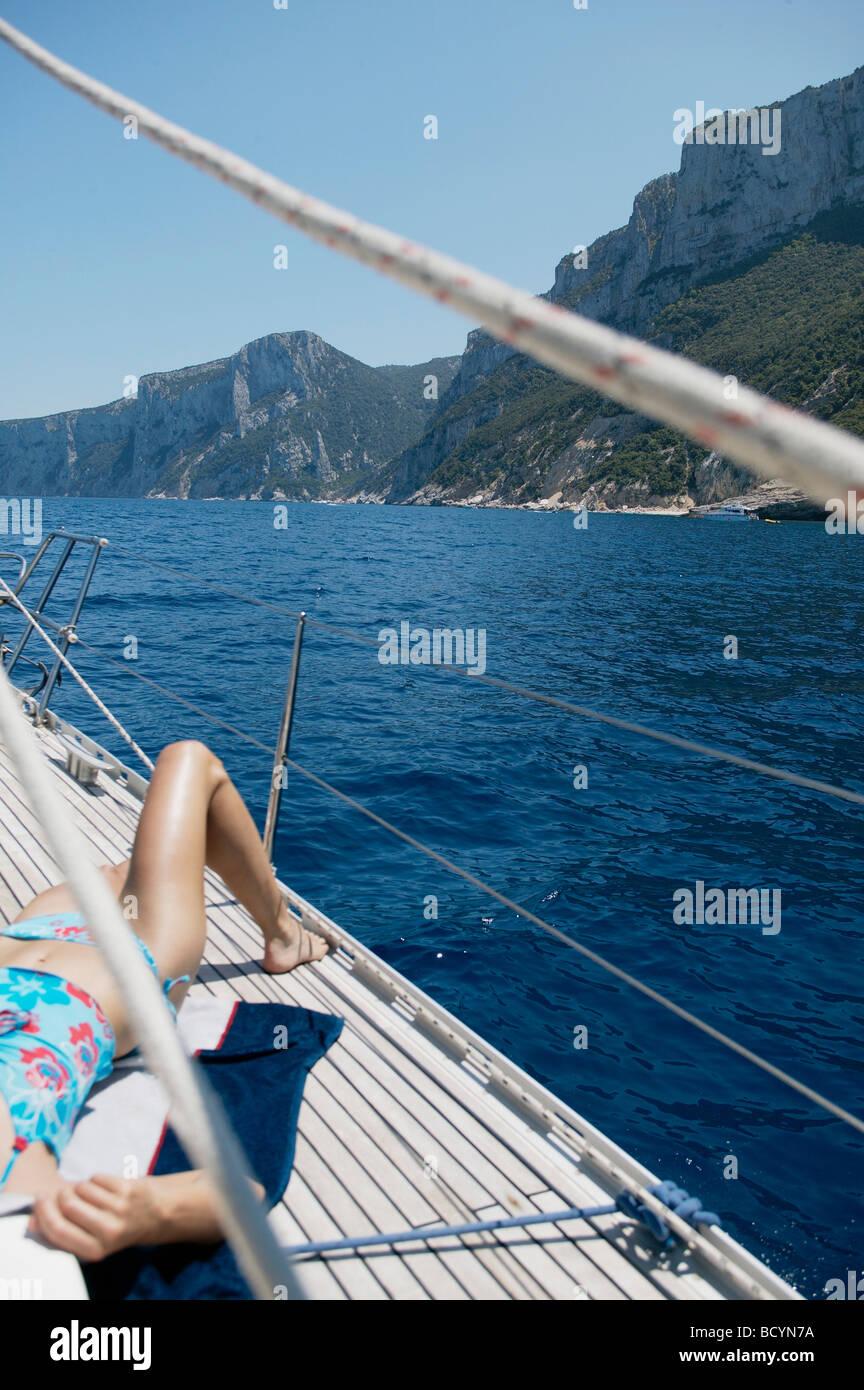 Woman sunbathing on Sailing Boat - Stock Image