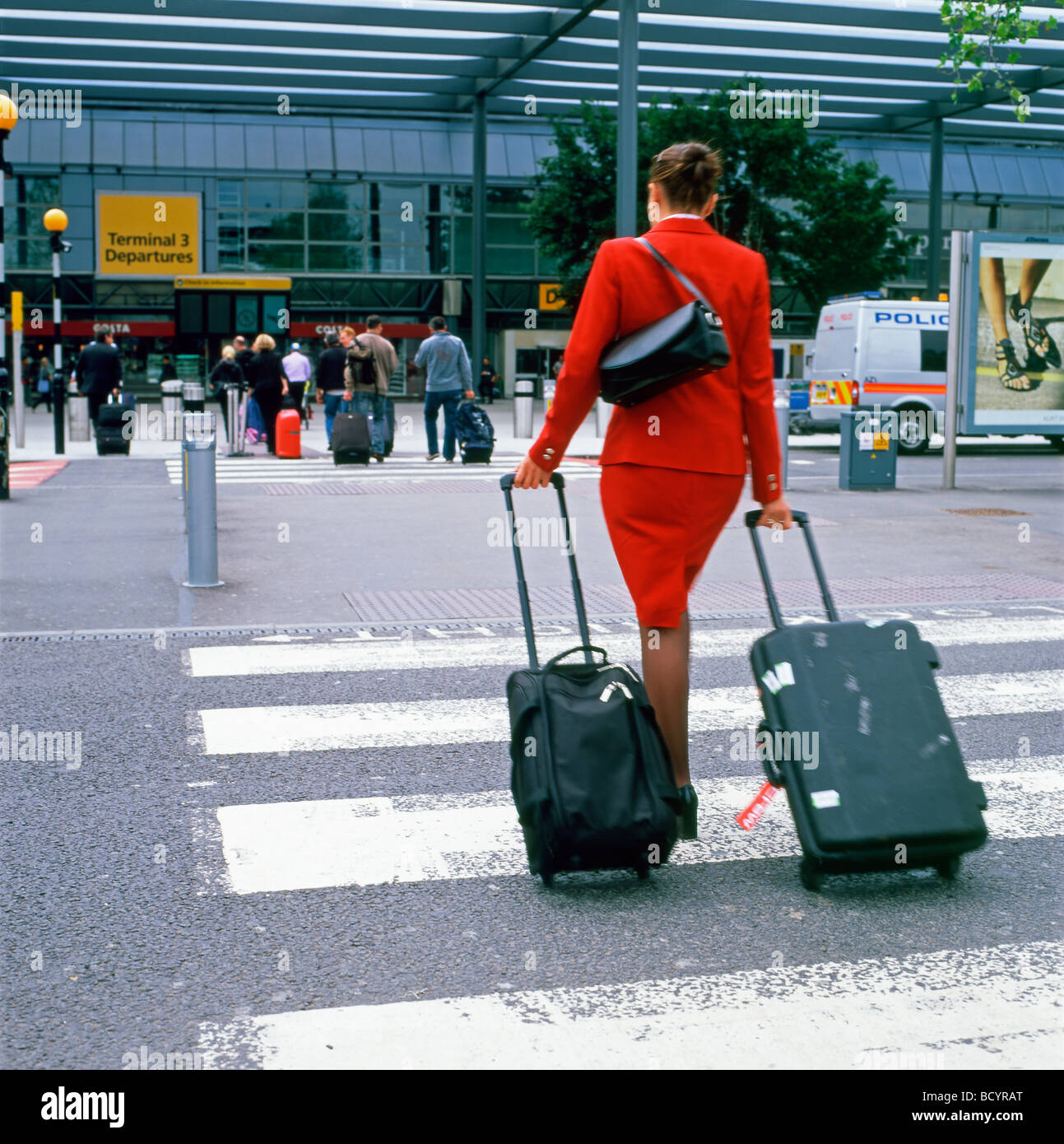 An air hostess with luggage on a crosswalk walking to Terminal 3 entrance Heathrow airport London England  KATHY - Stock Image