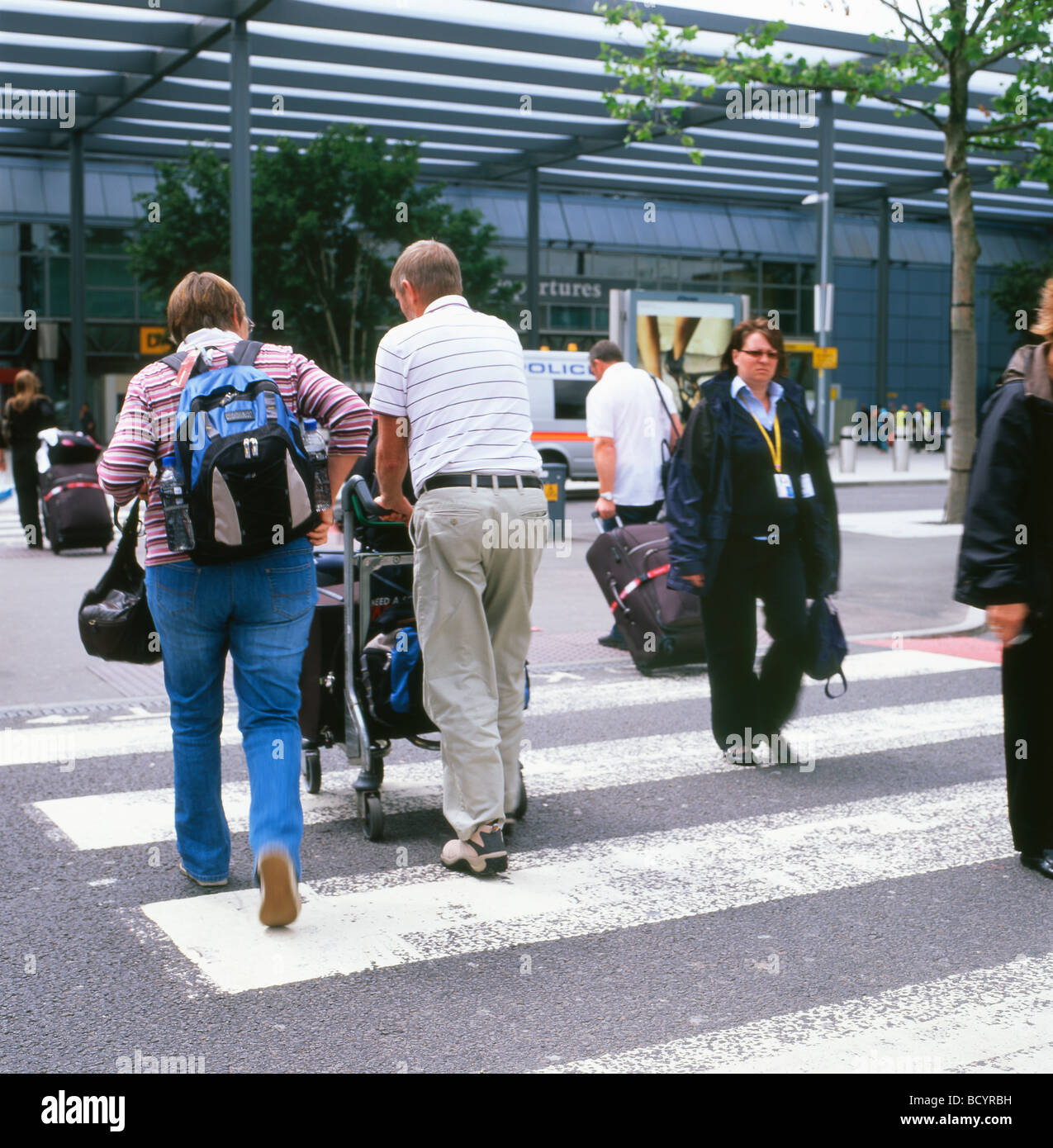 d60774d8f5044 Passengers pushing luggage on trolleys to the entrance of the departure  terminal 3 Heathrow Airport London