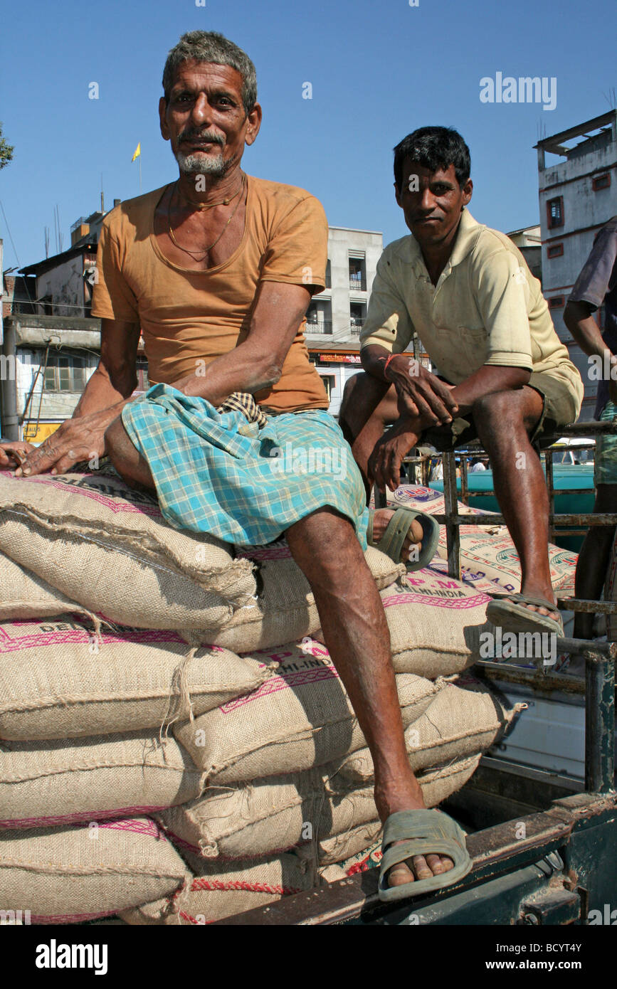 Two Indian Men Rest On Sacks Of Rice Taken In Jorhat, Assam State - Stock Image