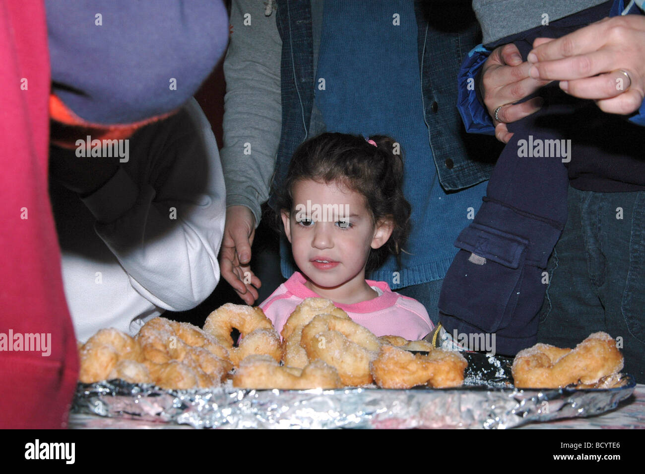 Israel Jordan Valley Kibbutz Ashdot Yaacov Eating Sufganyot during a Hanukah celebration - Stock Image
