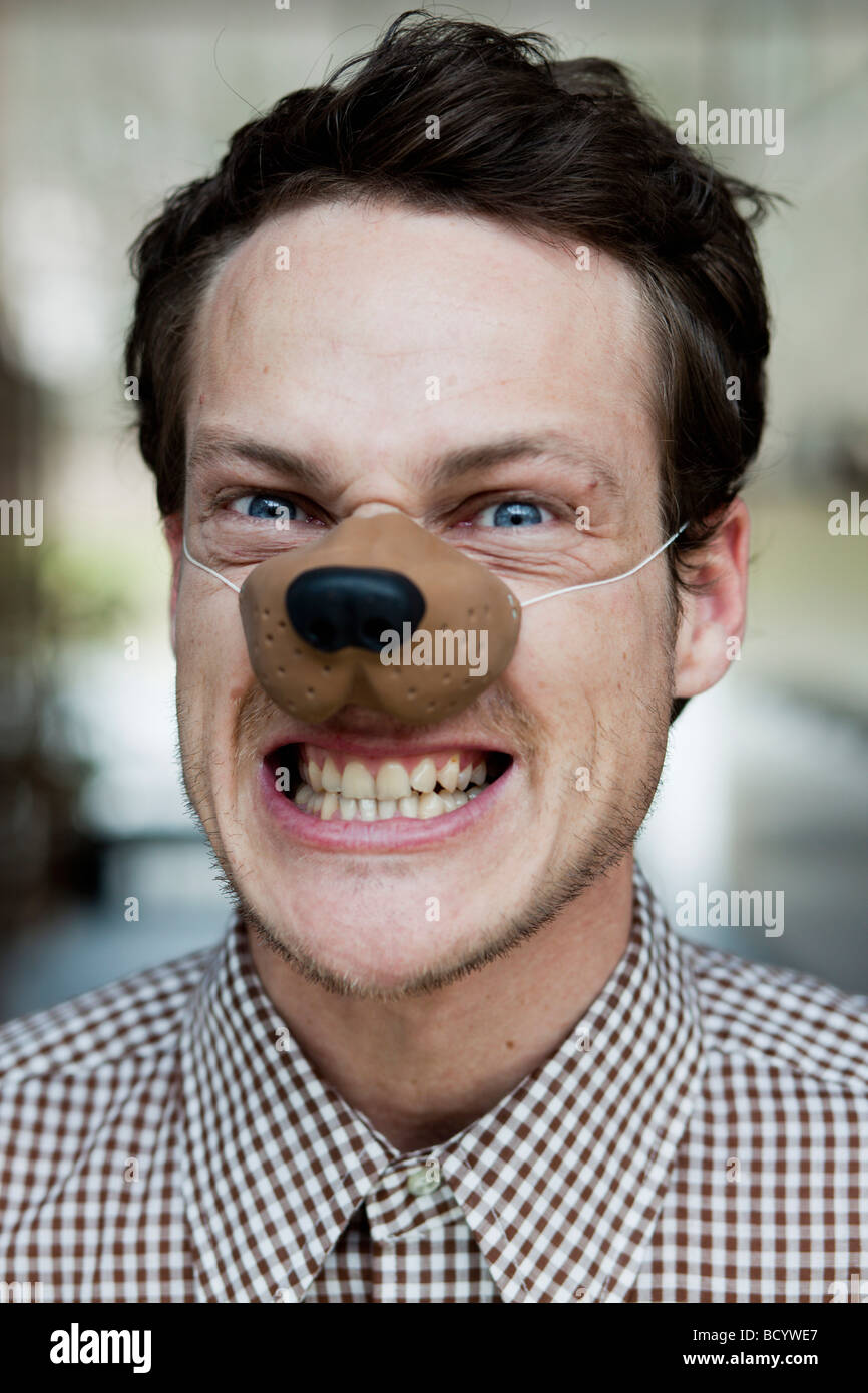man with toy dog nose snarling Stock Photo