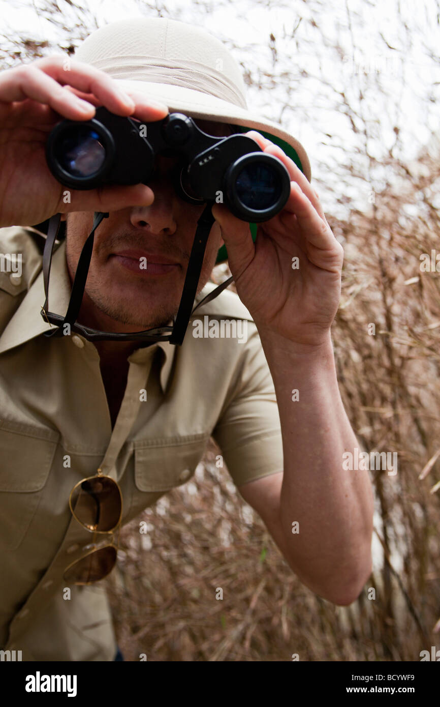 man in jungle outfit using binoculars - Stock Image