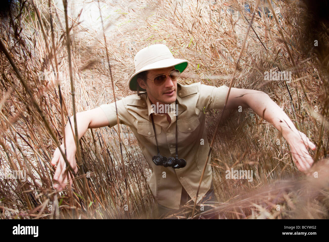 man in jungle outfit wading riverside - Stock Image