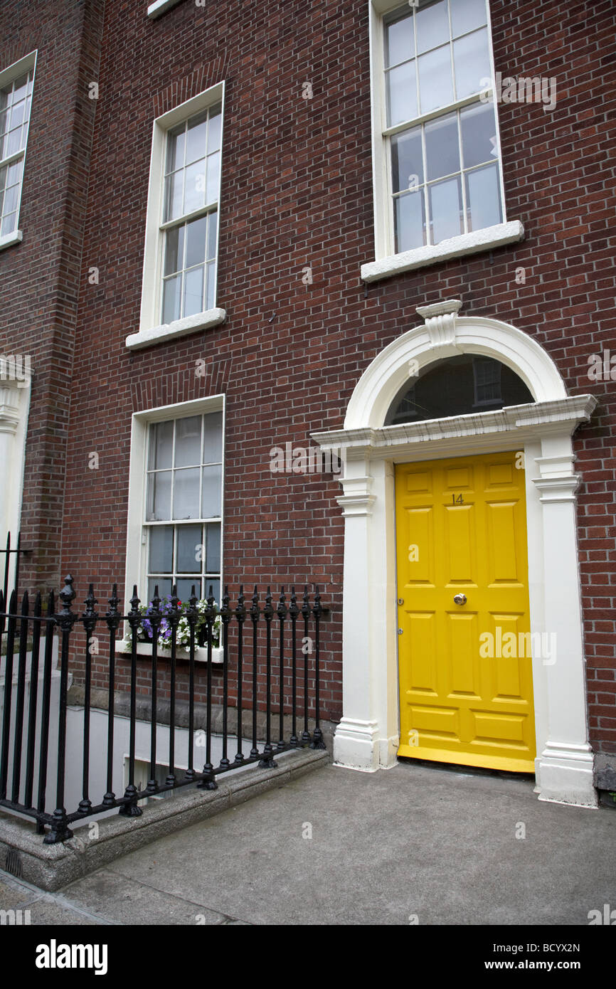 yellow painted georgian door on a red brick townhouse merrion square dublin republic of ireland - Stock Image
