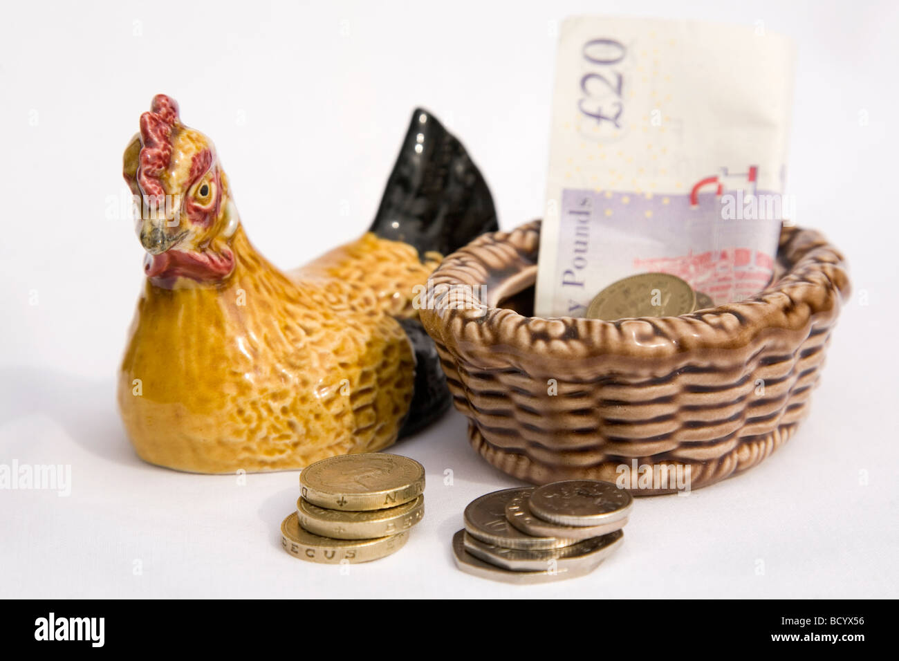 Coins are laid out next to a ceramic hen. A similar hen was used for the family to place money in,in the British - Stock Image
