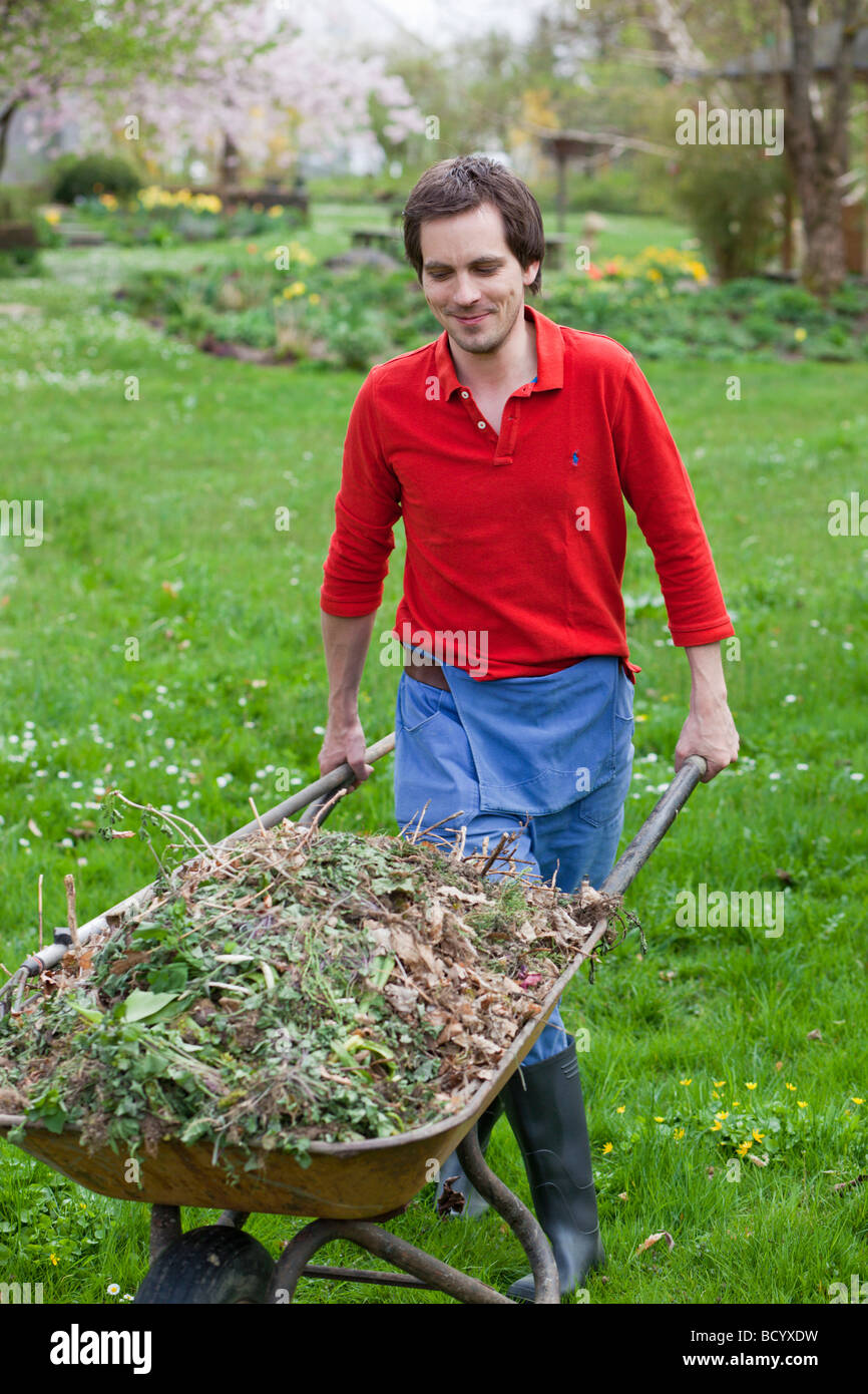 man pushing wheelbarrow - Stock Image