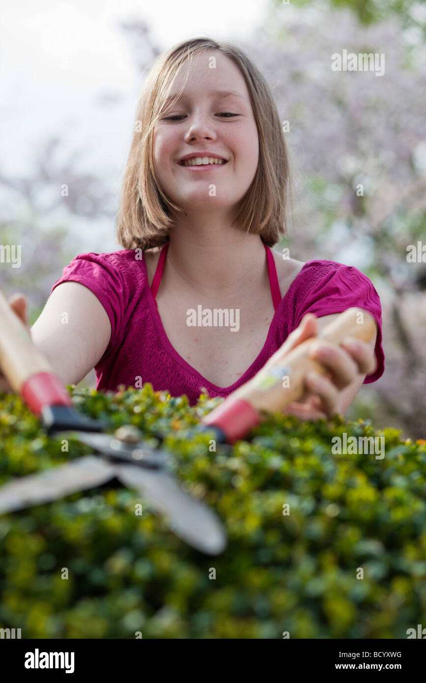 young girl cutting hedge - Stock Image