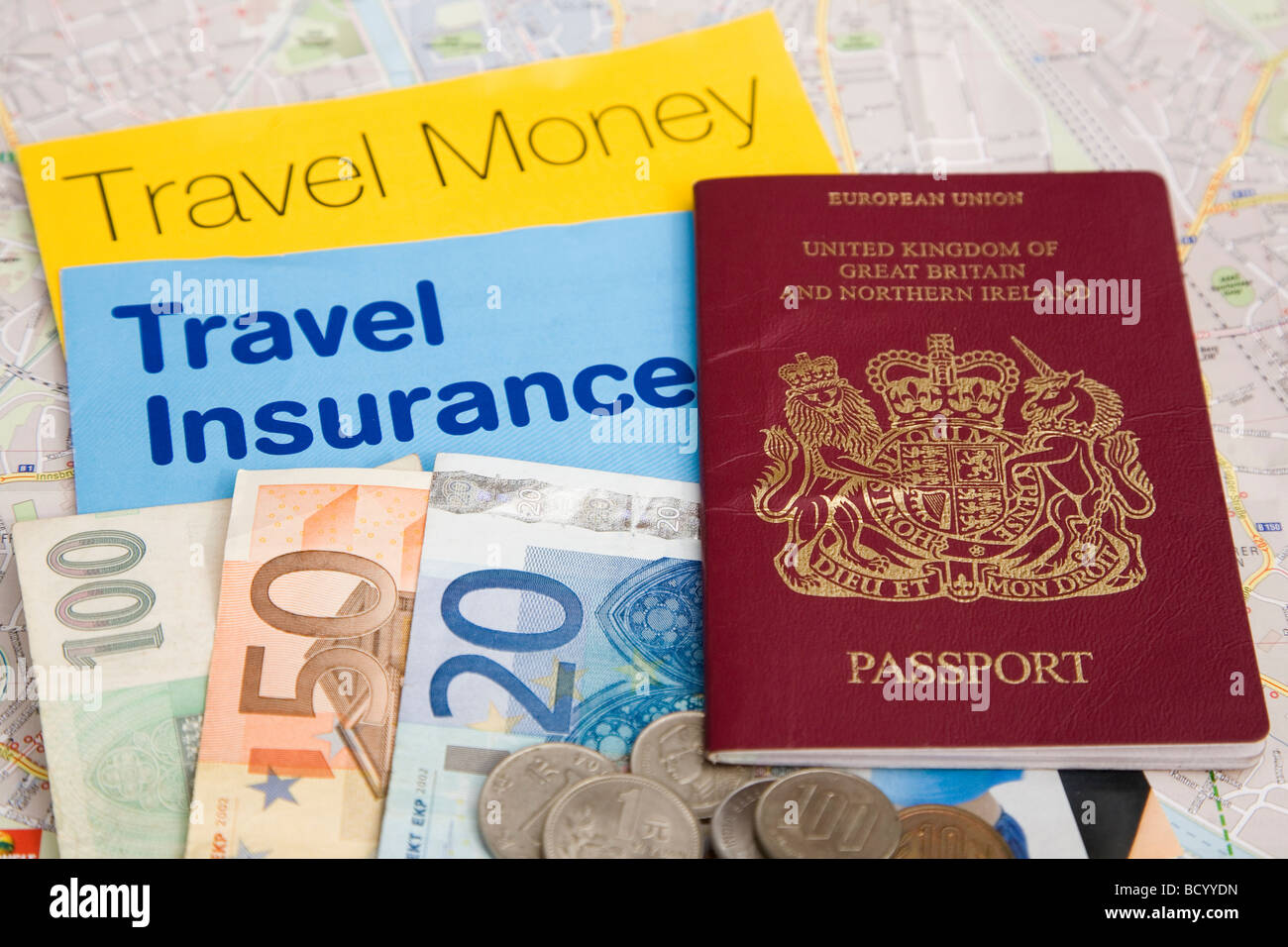 Preparation for a foreign vacation. A British EU passport travel insurance and travel money brochures can be seen. - Stock Image
