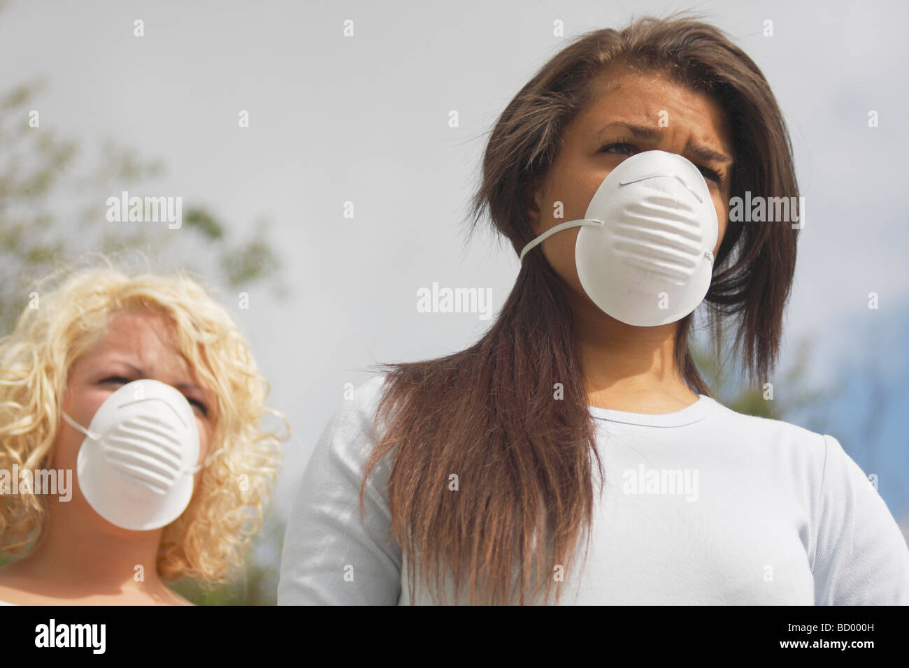 two young women in street wearing protective face filter masks - Stock Image