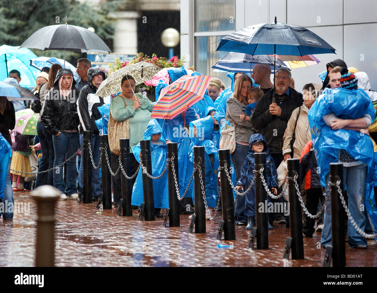 Visitors to the Sealife Centre in Birmingham, UK, queue outside in the rain. - Stock Image