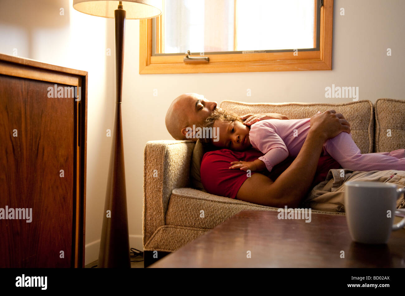 Dad and Child take a nap on the couch - Stock Image