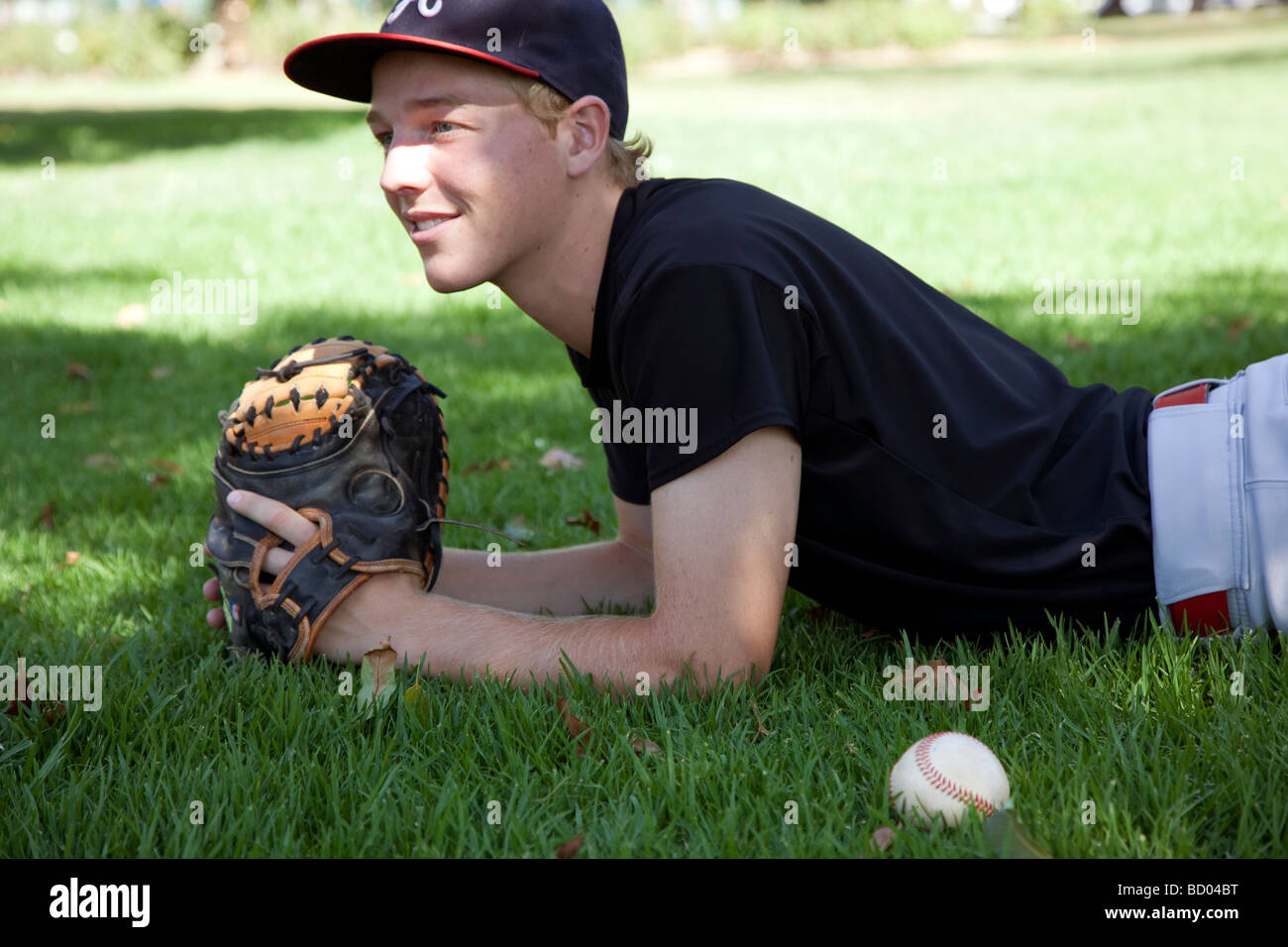 teenager lies on grass with base ball and catchers mit - Stock Image