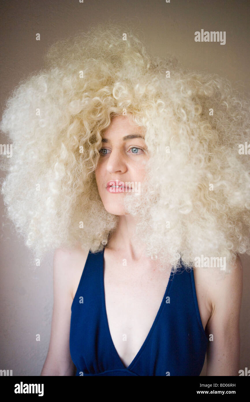 portrait of 70's woman with wild blond curly hair - Stock Image