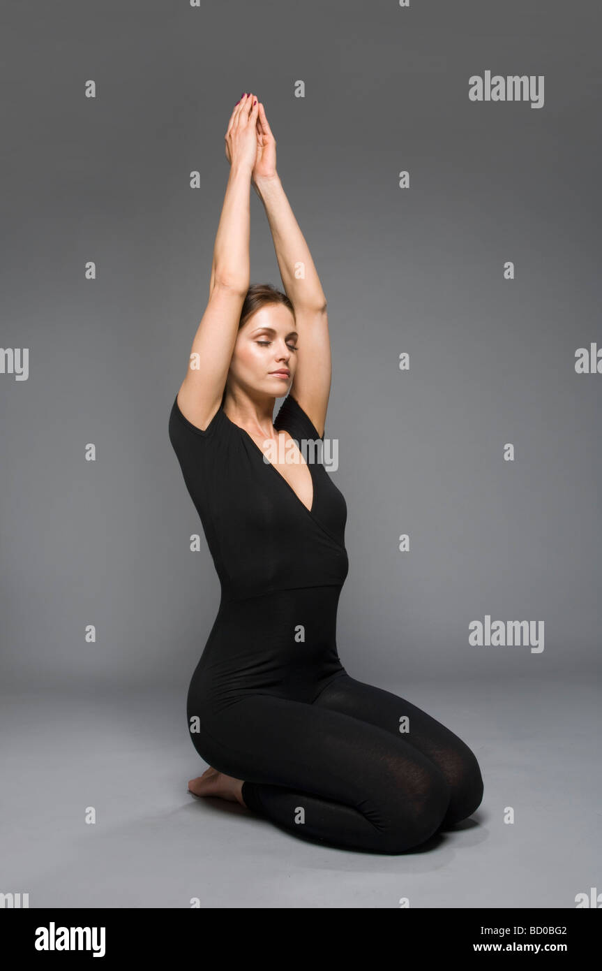 female beauty in catsuit yoga position - Stock Image