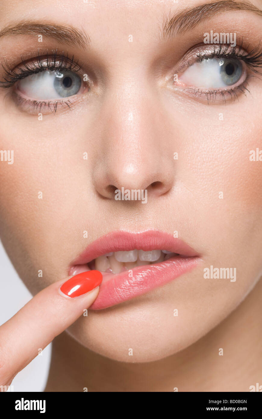 female beauty with finger in mouth - Stock Image