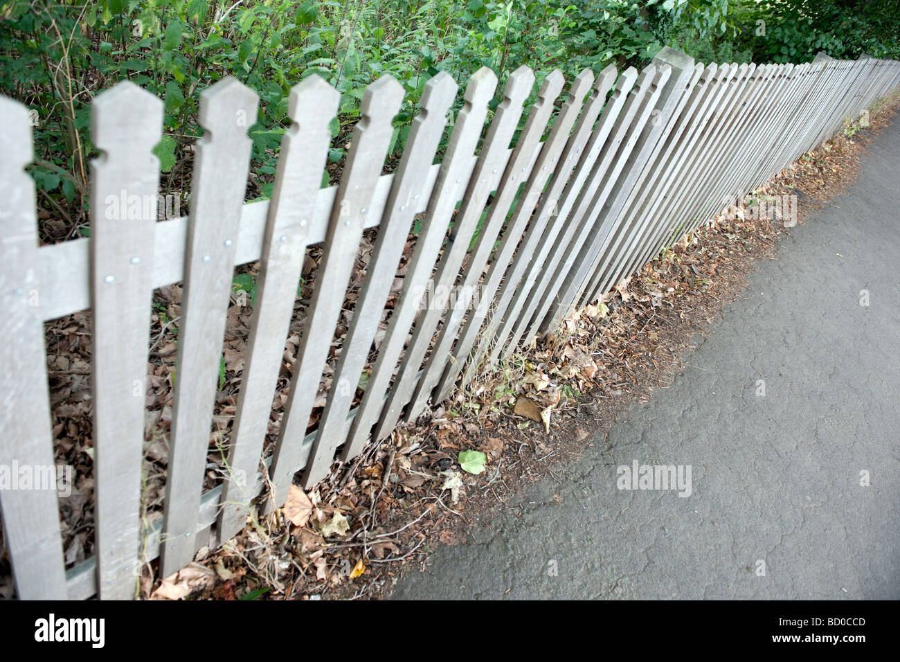 Unpainted picket fence with carved pales shot at an angle Stock Photo