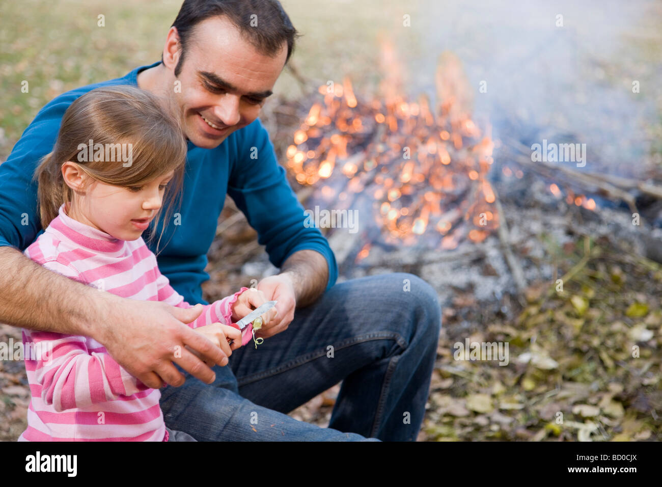 father helping daughter to carve stick - Stock Image