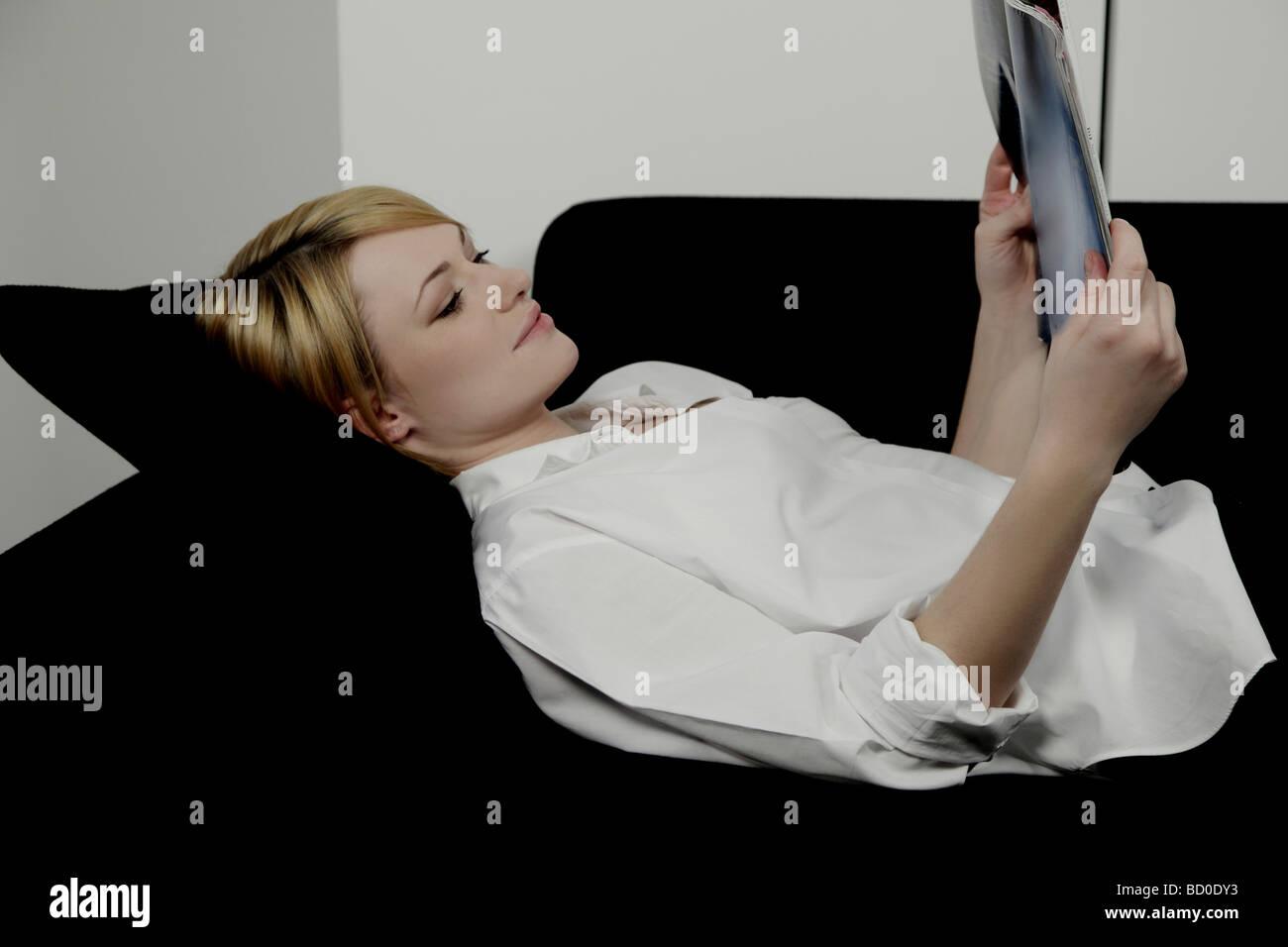 Woman laying on sofa reading magazine. - Stock Image
