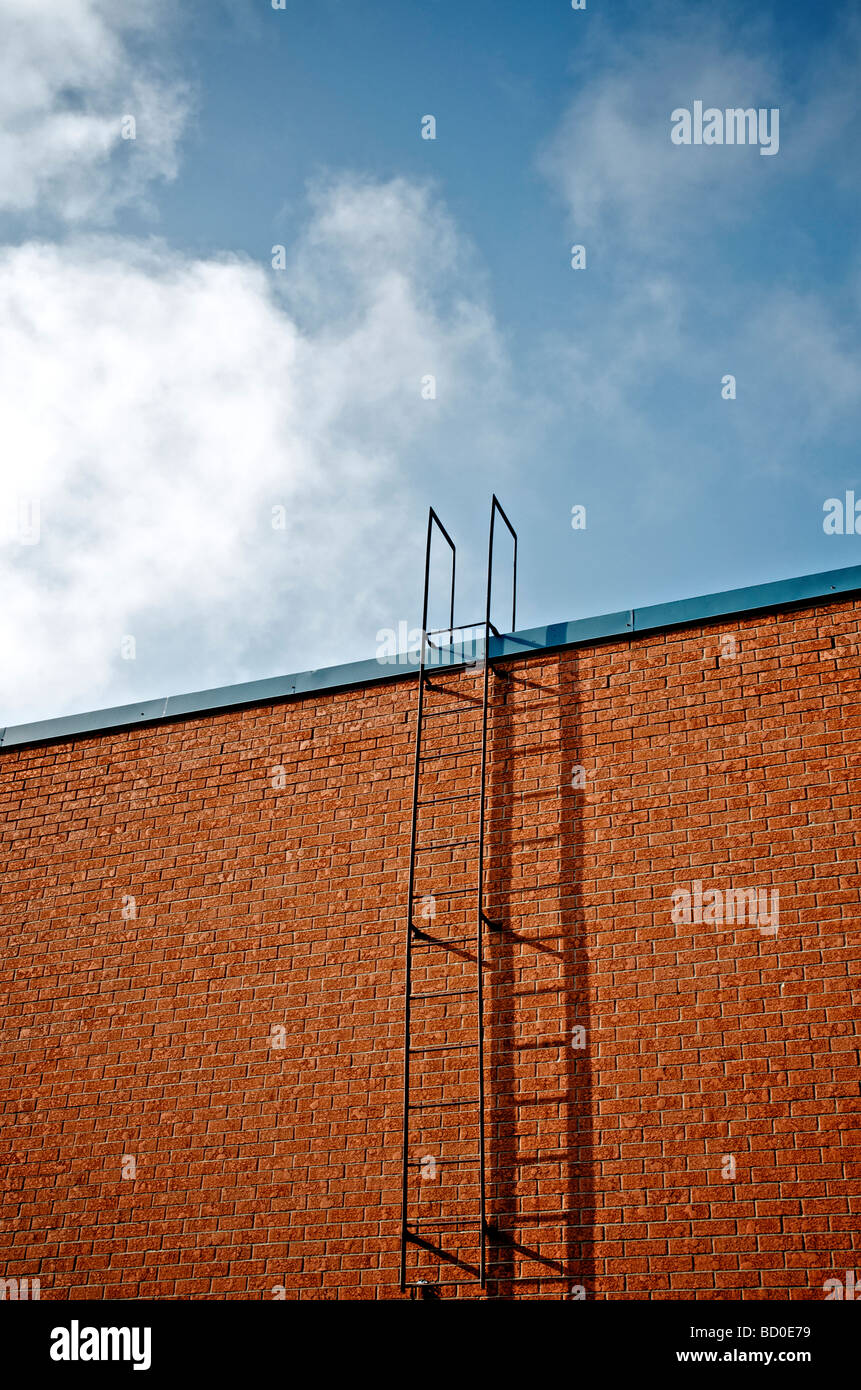 Ladder on the side of a brick wall and blue skies, Mont St-Hilaire, Quebec - Stock Image