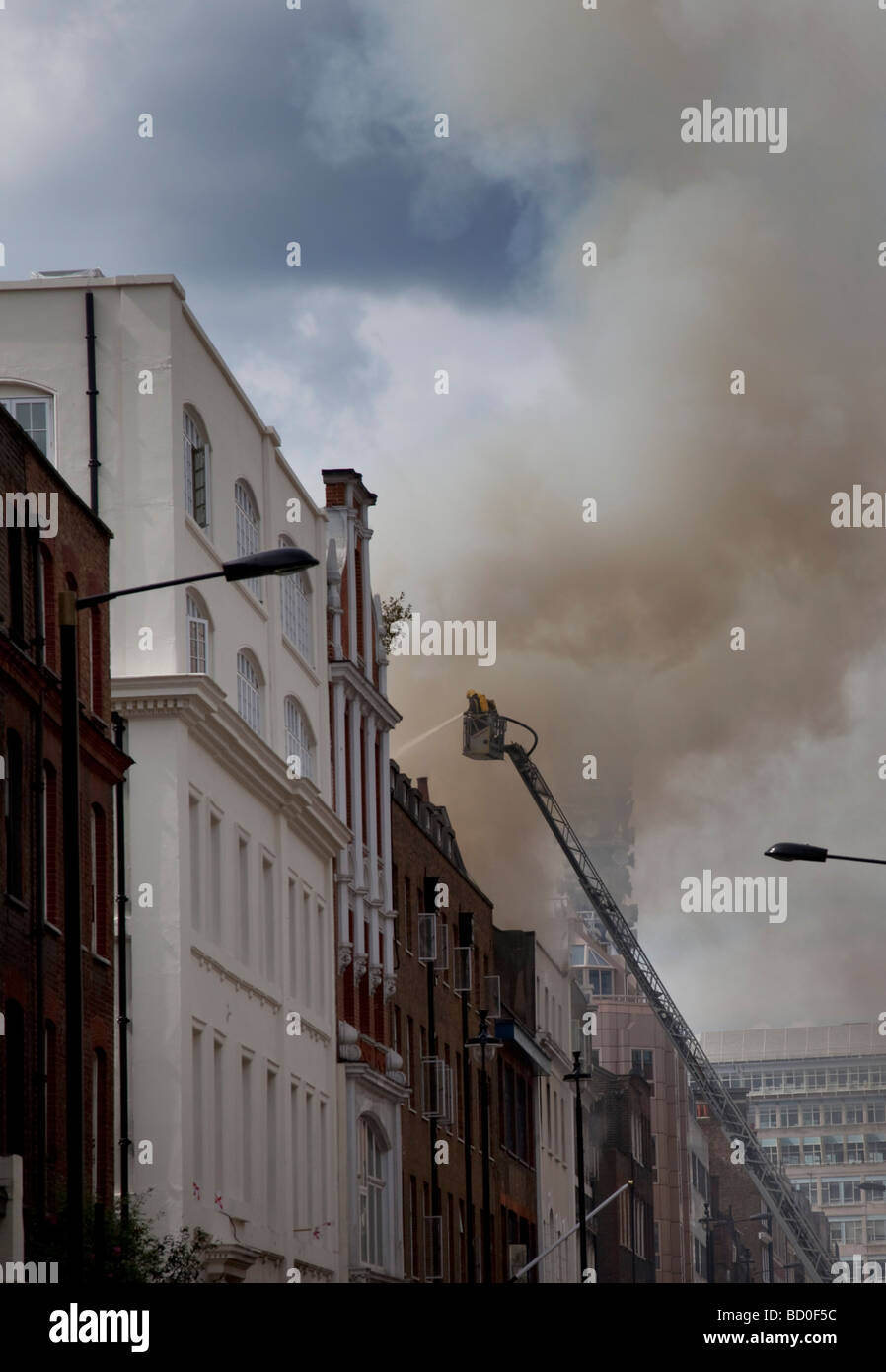 Firefighters battle a blaze in the heart of Soho, London after a fire in Dean Street destroyed a building. - Stock Image