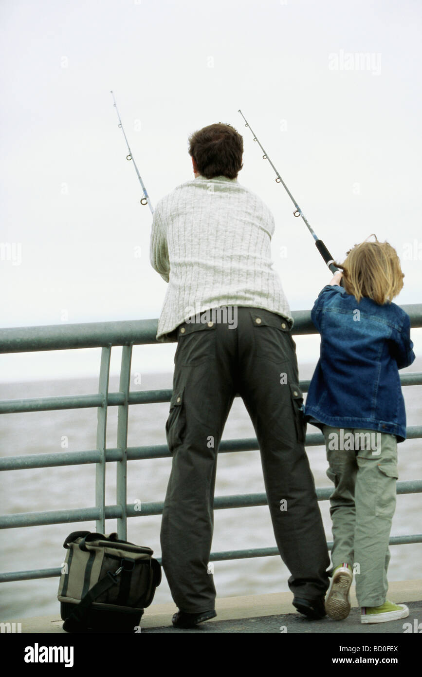 Father and son fishing from pier, rear view - Stock Image