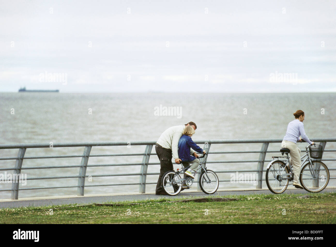Father helping son learn to ride bicycle at seaside park, mother riding ahead - Stock Image