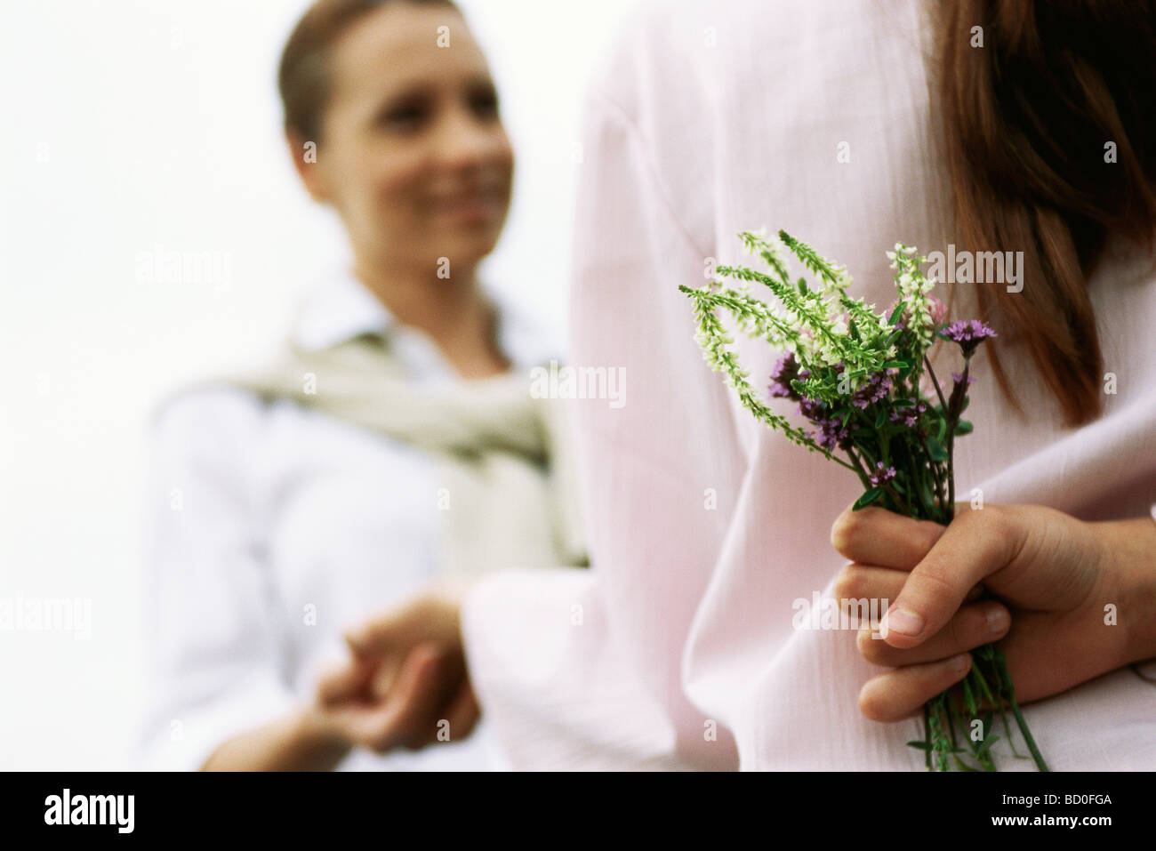 Girl hiding wildflower bouquet behind back, holding mother's hand, cropped - Stock Image