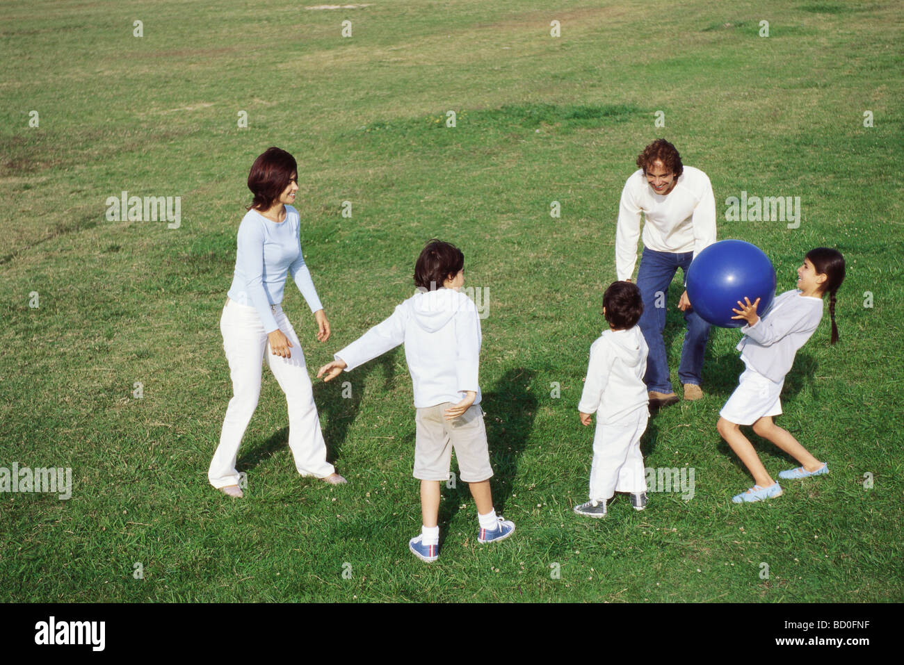 Family playing with ball in grassy field Stock Photo
