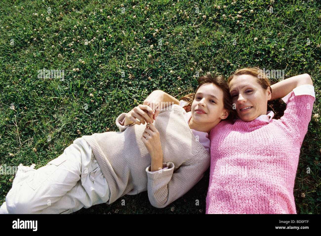 Mother and daughter lying together on grass, smiling at camera - Stock Image