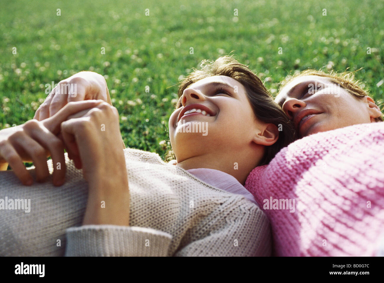 Mother and daughter reclining together on grass, girl resting head on mother's shoulder Stock Photo
