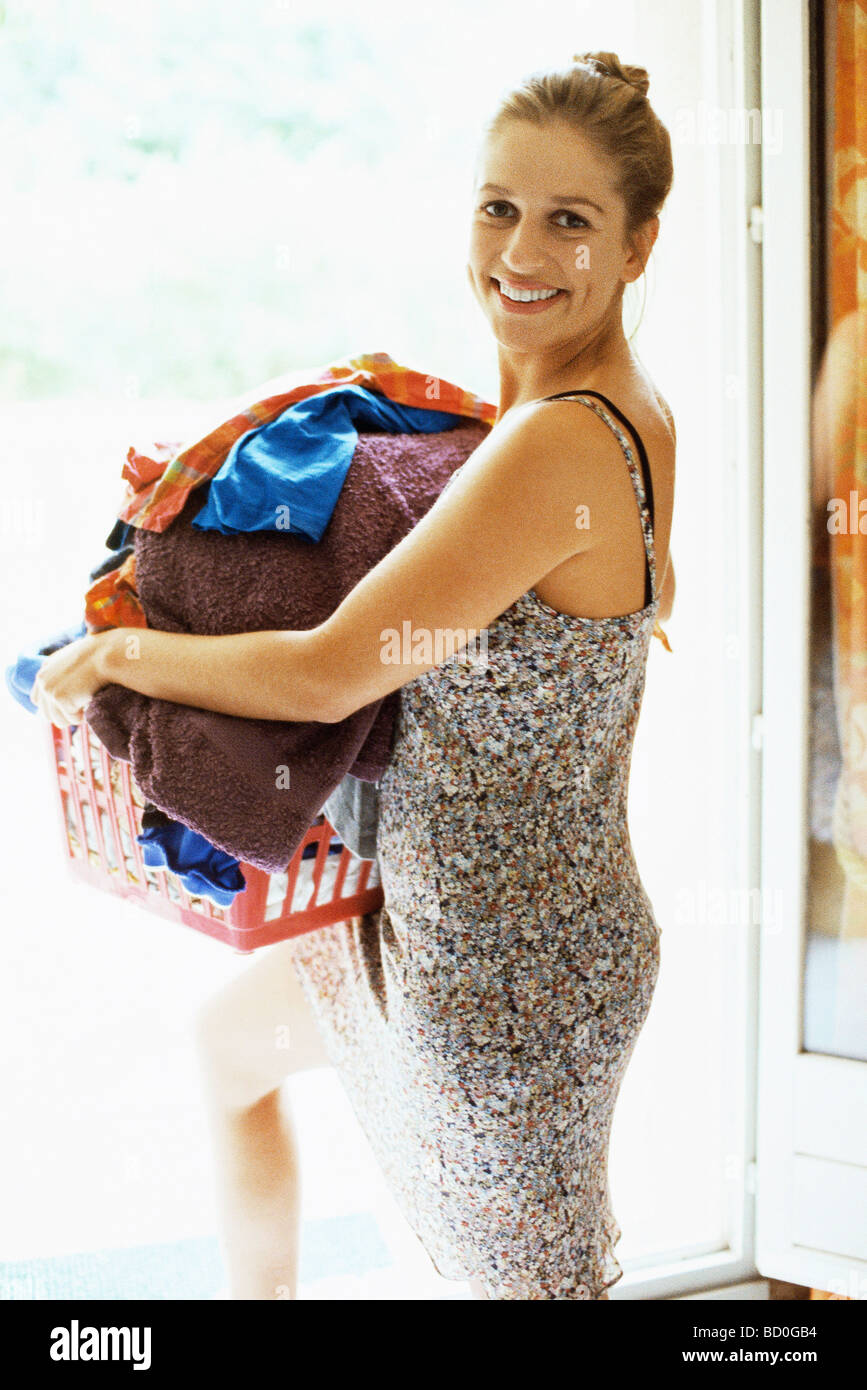 Woman carrying full laundry basket looking over shoulder at camera smiling - Stock Image