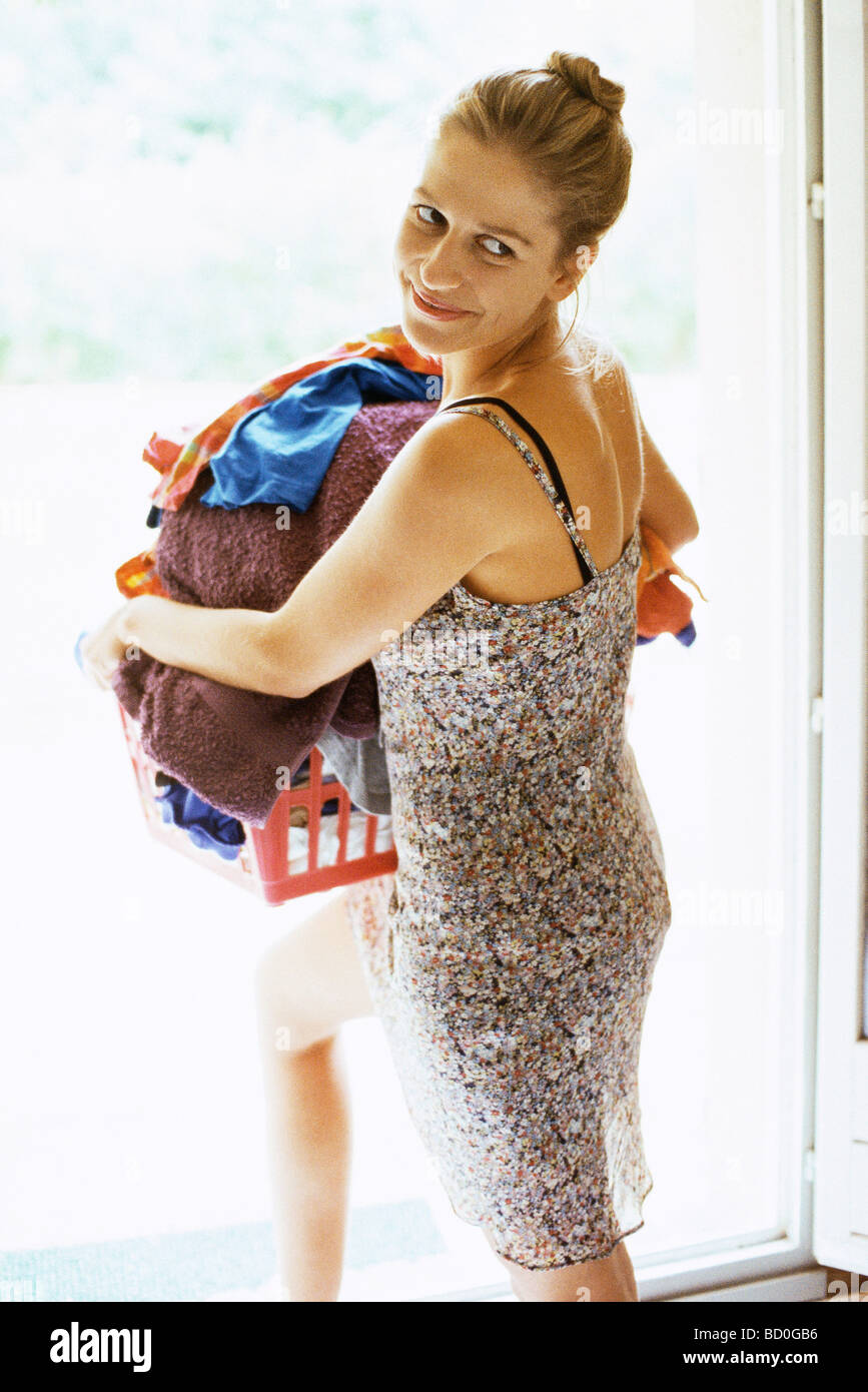 Woman carrying full laundry basket glancing sideways over shoulder - Stock Image