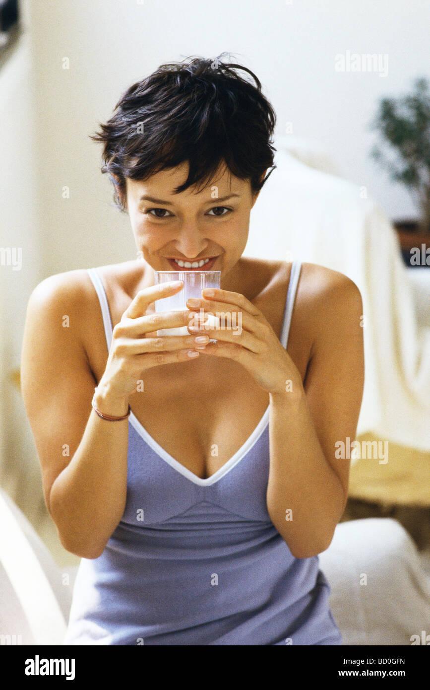 Woman drinking glass of milk - Stock Image