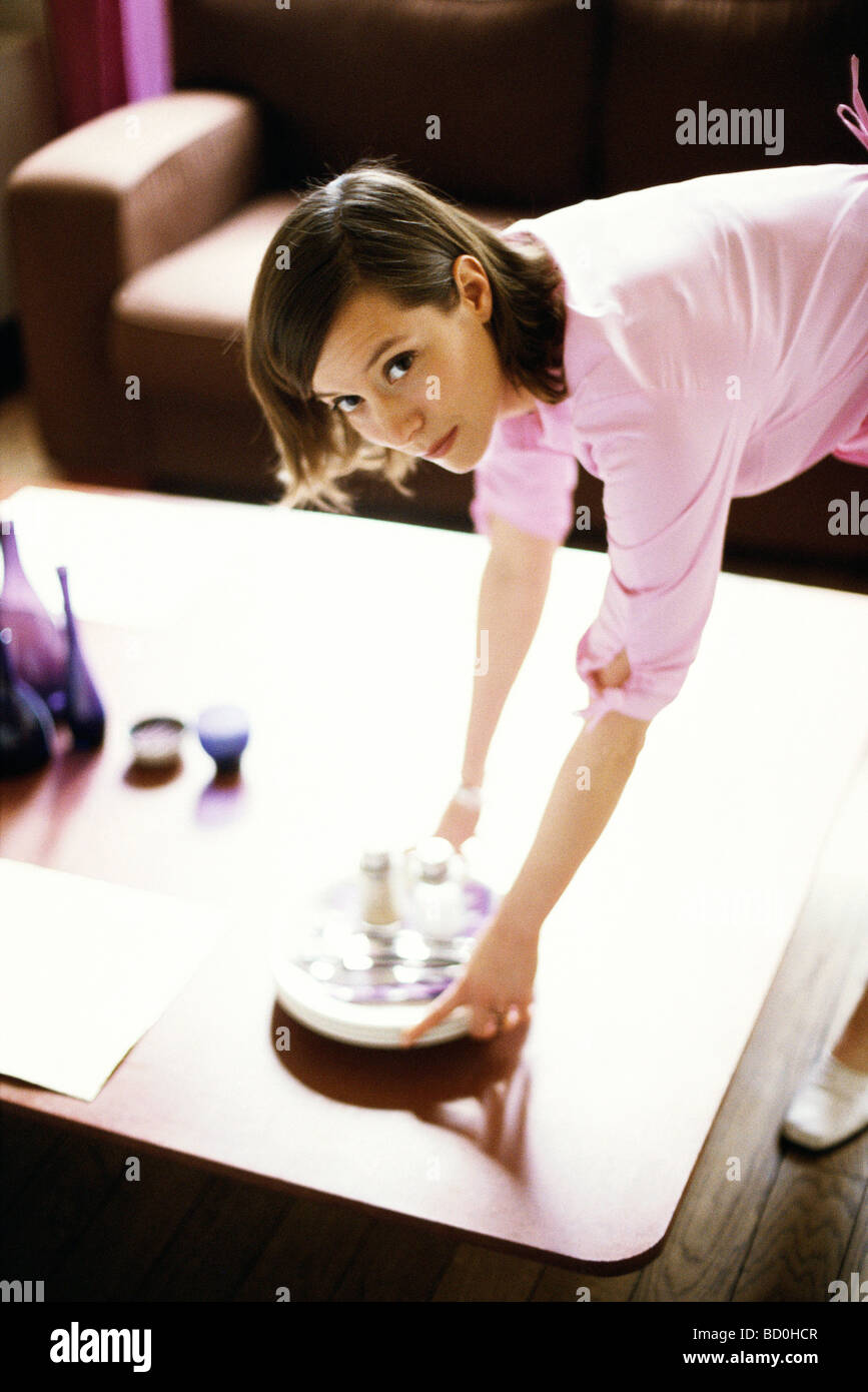 Woman placing dishes on coffee table - Stock Image