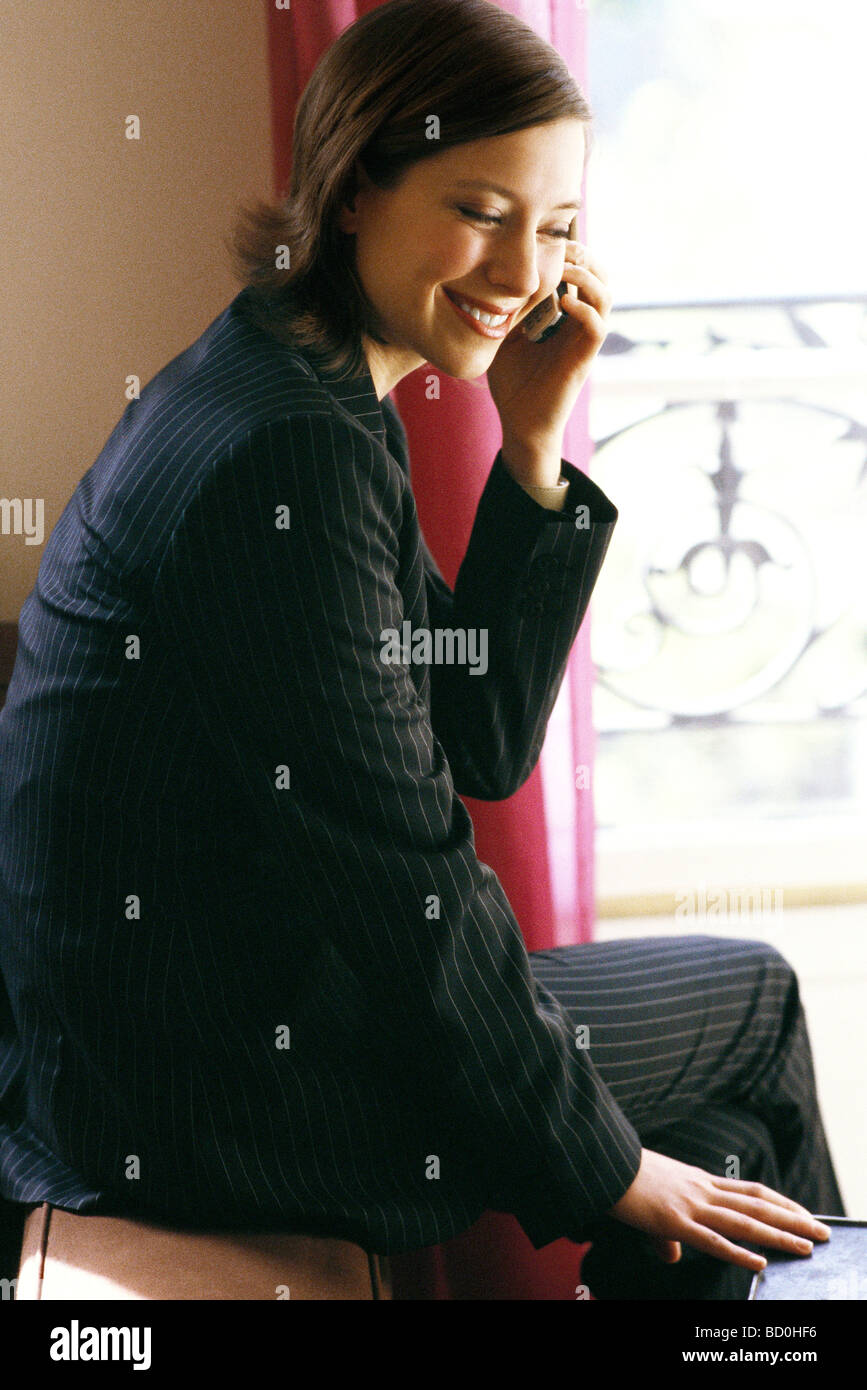 Woman in full suit sitting by window using cell phone - Stock Image