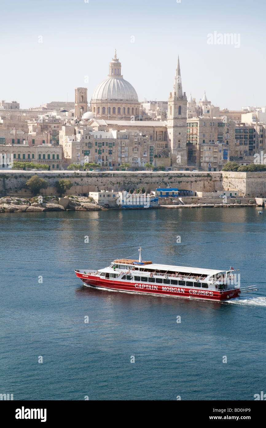 A tourist cruise and the skyline of Valletta, Malta, from Sliema - Stock Image