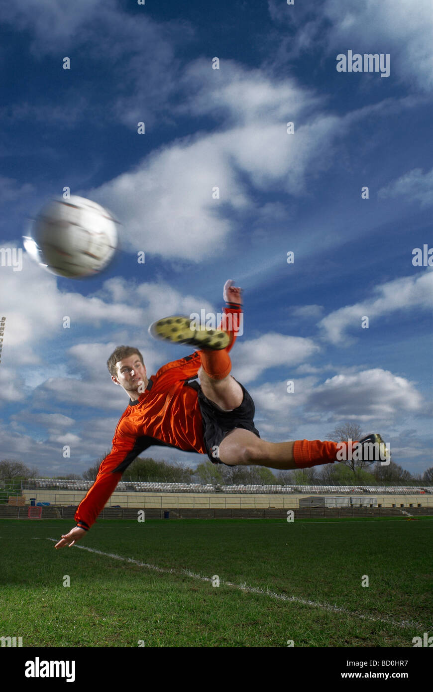 footballer volleying ball mid air - Stock Image