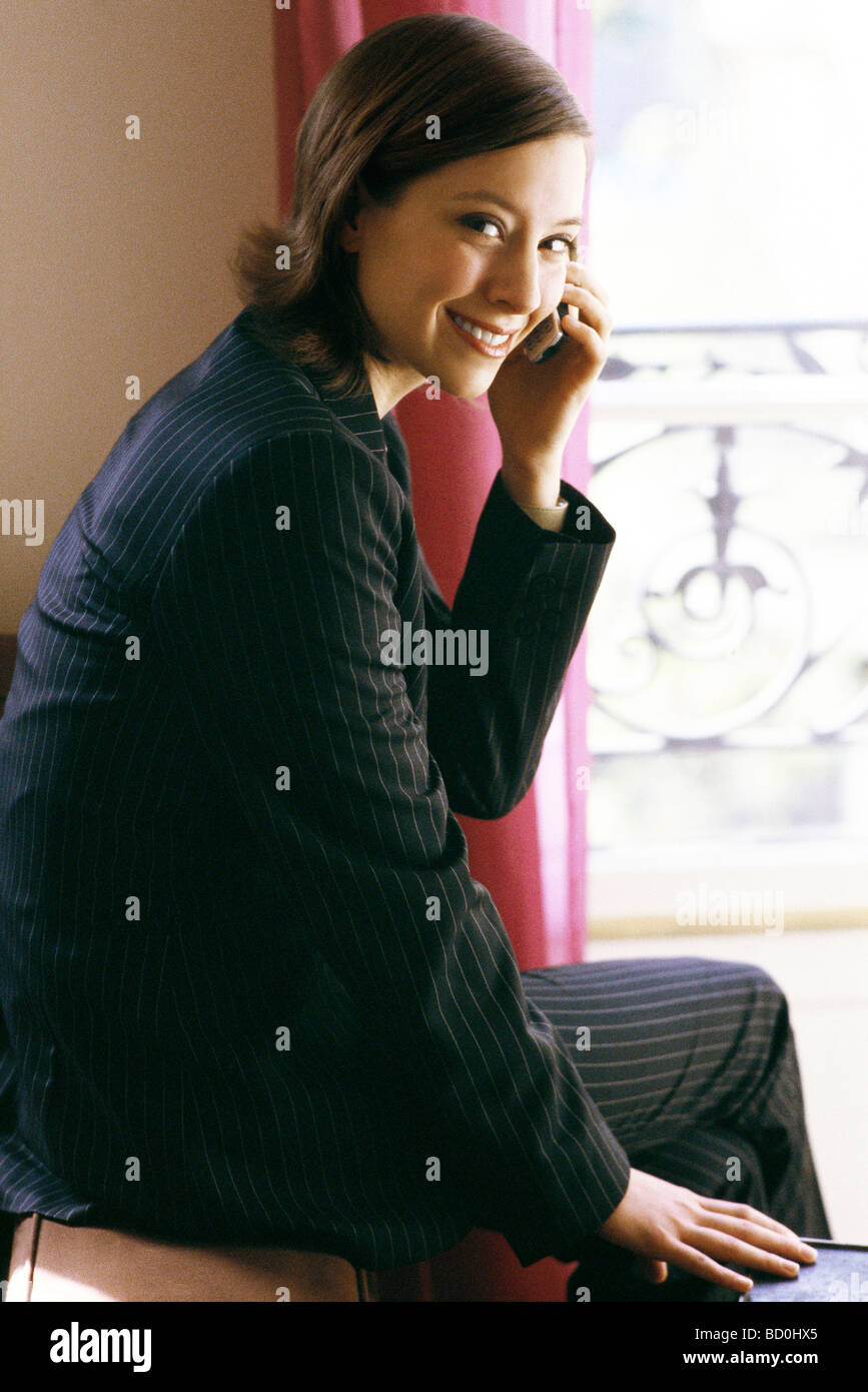 Young woman in suit sitting by window using cell phone - Stock Image