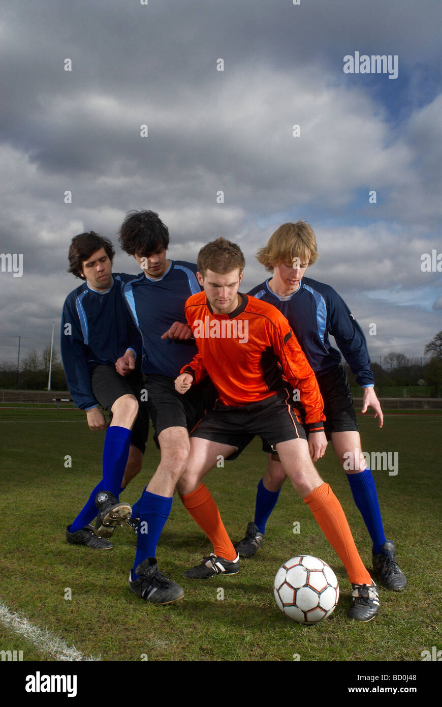 footballer surrounded by opposition - Stock Image