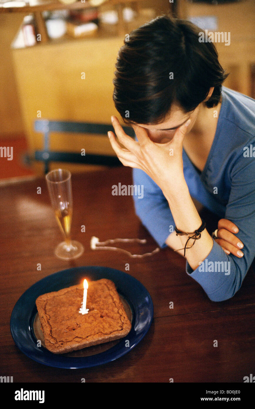 Woman sitting at table alone with anniversary cake, covering eyes - Stock Image