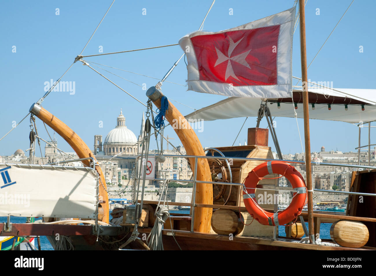 The maltese cross flag aboard a sailing boat with Valletta in the background, Malta - Stock Image