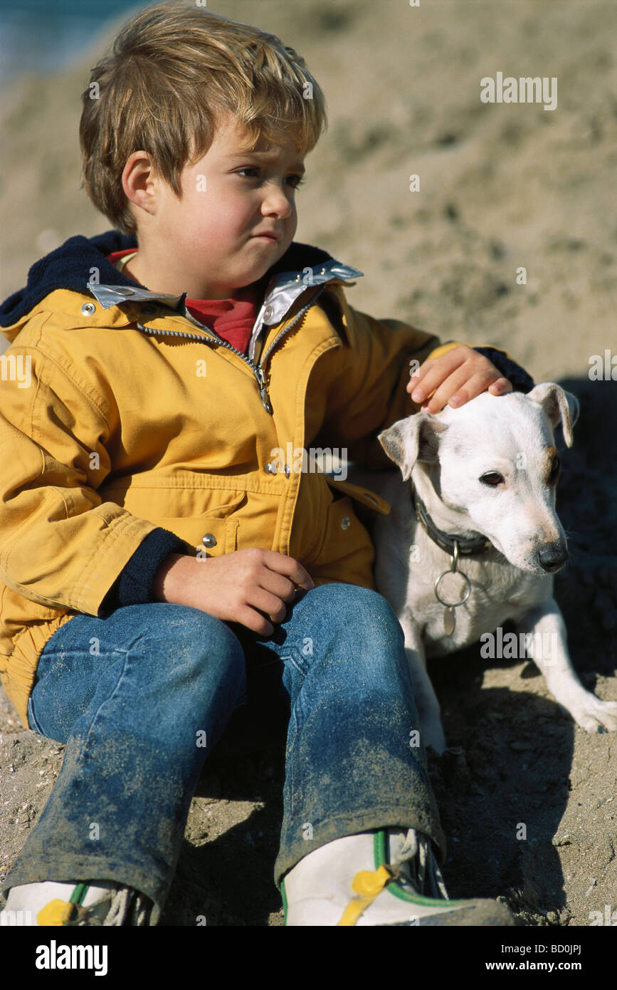 Little girl sitting outdoors with dog - Stock Image
